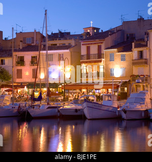 Cassis, Provence, France. View across the illuminated harbour at dusk. - Stock Photo