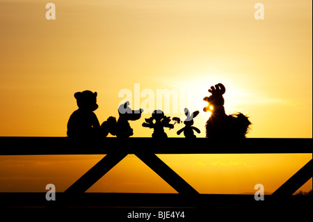 Rag doll, chicken, fox, rabbit and bear soft toys sitting on a gate at sunset in the English countryside. Silhouette - Stock Photo
