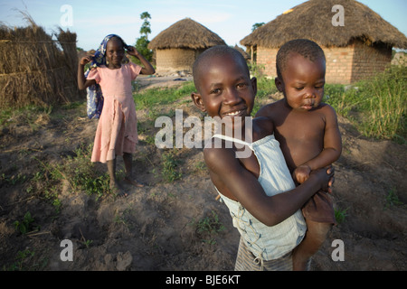 A young girl and her baby brother ouside their house in Amuria, Uganda, East Africa. - Stock Photo