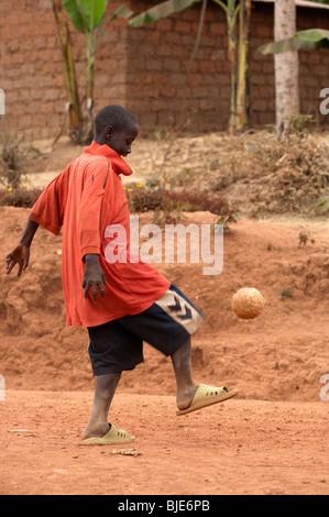 Young boy playing football in the Village street, near Kigali, Rwanda - Stock Photo