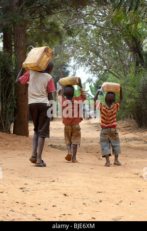 Children collecting water from well and carrying home. - Stock Photo