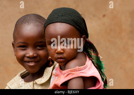 Two sisters, one carrying the other. Rwanda - Stock Photo