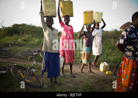 Children draw water from a watering hole in Amuria District, Uganda, East Africa. - Stock Photo