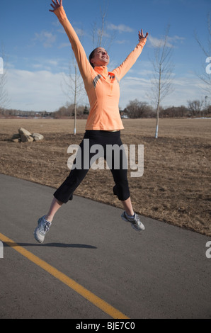 Woman jumping for joy in park - Stock Photo