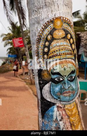 India, Kerala, Varkala, Kathakali dancer figure painted on coconut tree trunk - Stock Photo