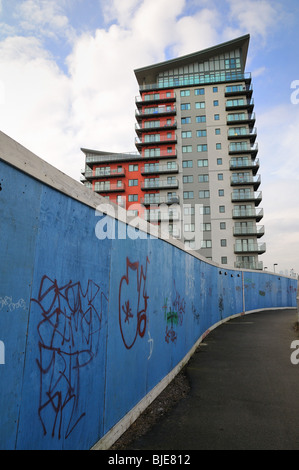 Modern apartment block at Woolwich with graffiti on hoarding - Stock Photo