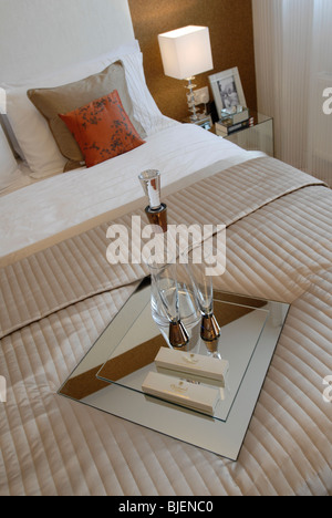 Wine carafe and glasses on silk bedding in luxury bedroom - Stock Photo