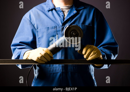 man in blue coveralls with a power grinder - Stock Photo