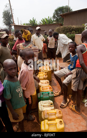 Children collecting water from well and carrying home. Rwanda - Stock Photo