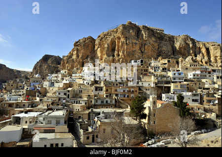 The Christian village of Maloula, or Maalula, beneath limestone cliffs, a pilgrim destination in Syria - Stock Photo