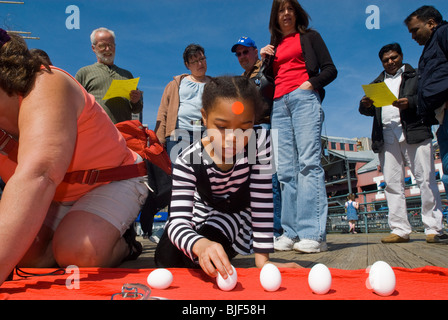 Participants gather at the South Street Seaport in New York to welcome the arrival of spring by standing raw eggs - Stock Photo