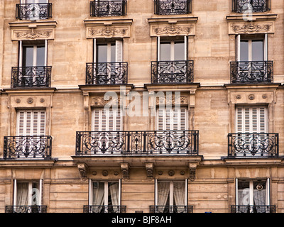 Ornate apartment block exterior with balcony in Paris, France, Europe - Stock Photo