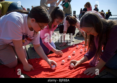 Participants gather at the South Street Seaport in New York to stand eggs on end to welcome the arrival of spring - Stock Photo