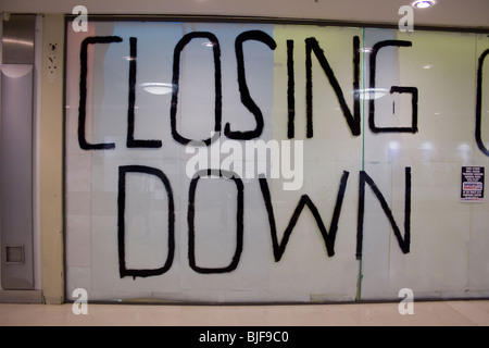 Closing Down written in big letters on a shop window - Stock Photo