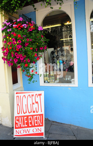 A sale sign with a colourful flower pot outside a clothes store in the UK