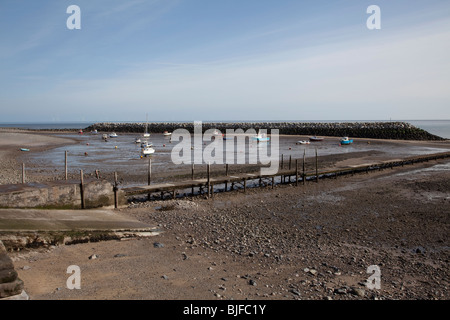Man made harbour with small boats during low tide at Rhos on Sea holiday resort North Wales, Britain - Stock Photo