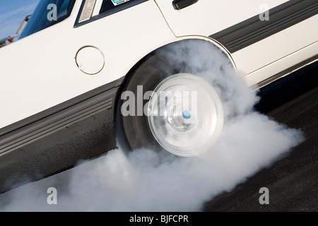 Close up of spinning car tire and wheel performing a smoking burnout - Stock Photo