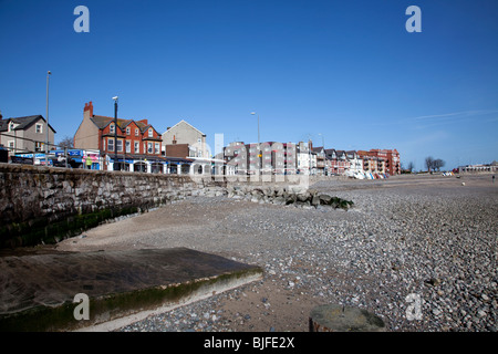 Rhos on Sea, North Wales seafront shops and accommodation viewed from the beach within a rocky breakwater - Stock Photo