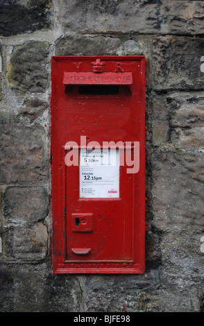 Red Victorian post box set in a wall. - Stock Photo