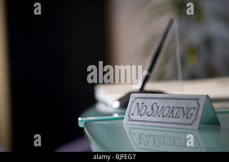 Close up of no smoking sign on glass desk - Stock Photo