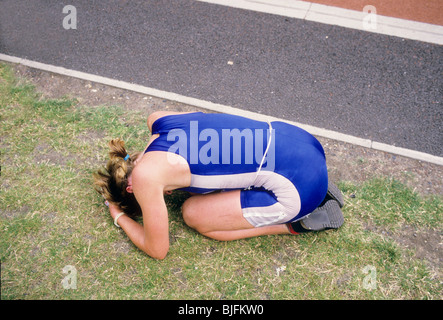 Disappointed kneeling on grass after race - Stock Photo