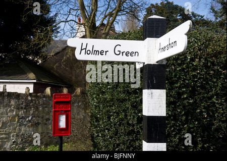 traditional village signpost and red letter box in Little Missenden Bucks UK. - Stock Photo
