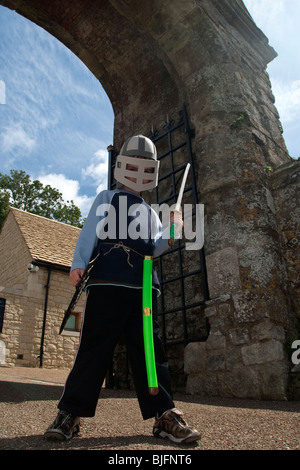 Young Boy Pretending To Be A Knight in Armour Outside Carisbrooke Castle on the Isle Of Wight - Stock Photo