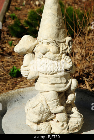 A garden Gnome or Norse dwarf guarding the earths minerals and stones. - Stock Photo