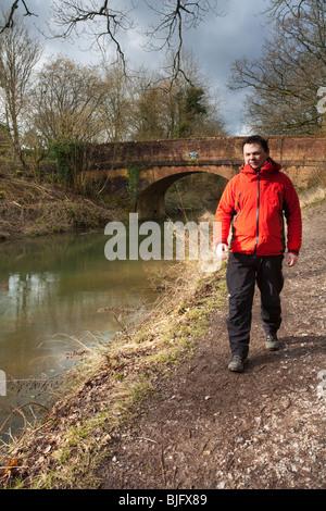 Male walker on the towpath of the Basingstoke Canal by Broak Oak Bridge near Odiham, Hampshire, Uk - Stock Photo