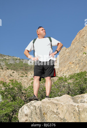 adult male hiker standing on rock ledge looking ahead - Stock Photo
