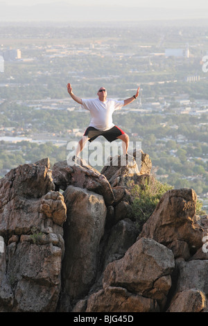 large adult male hiker standing on top of mountain in yoga pose - Stock Photo
