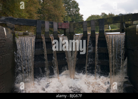 Water cascades through 'overflow' gates of a lock on the Rochdale canal, Yorkshire, UK. - Stock Photo