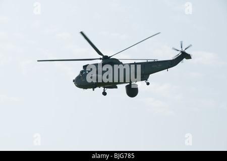 A Royal Navy Westland Sea King ASaC flies past the visitor center at RNAS Culdrose - Stock Photo