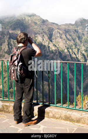 A man uses binoculars to look into the Valley of the Nuns on the island of Madeira, Portugal. - Stock Photo