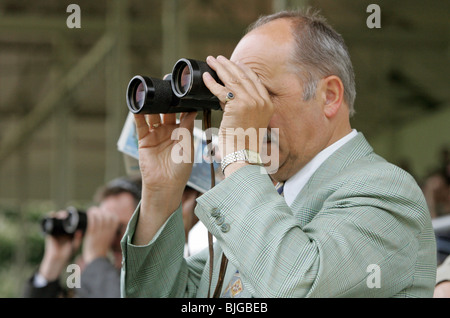 A man looking through binoculars at horse races, Iffezheim, Baden-Wurttemberg - Stock Photo