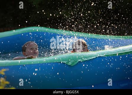 Kids playing in paddling pool - Stock Photo