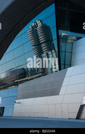 BMW HQ and museum reflected in the BMW Welt building, Munich, Germany. - Stock Photo