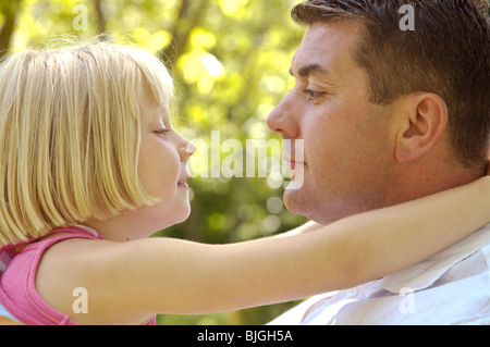 Close up of father and daughter with arms around neck