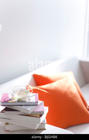 Herbal tea and a pile of books on a sofa - Stock Photo