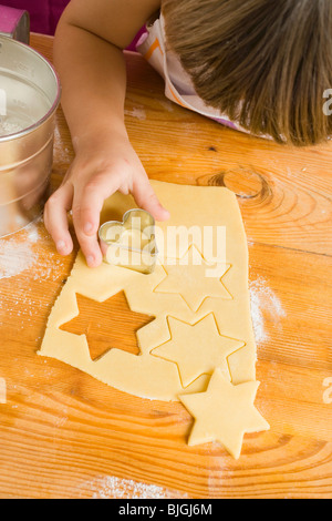 Child cutting out biscuits (overhead view) - - Stock Photo