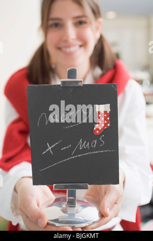 Young woman holding slate with the words Merry X-mas (for table) - - Stock Photo