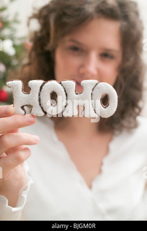 Woman holding biscuit (the word HOHO) - - Stock Photo