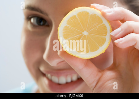 Young woman holding lemon in front of her eye - - Stock Photo