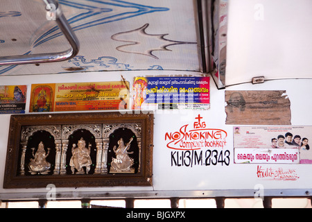 India, Kerala, Calicut, Kozhikode, Hindu deities and No Smoking sign on inside of local bus - Stock Photo