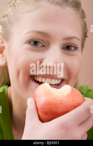 Woman holding partly eaten apple - - Stock Photo