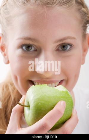 Woman eating green apple - - Stock Photo