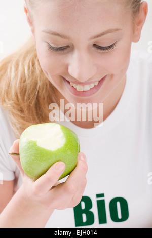 Woman eating an organic green apple - - Stock Photo