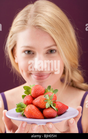 Woman holding a plate of strawberries - - Stock Photo