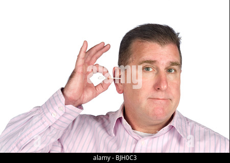 A middle aged man cleans his ear with a cotton swab. - Stock Photo