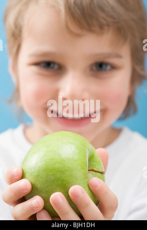 Little boy holding green apple - - Stock Photo